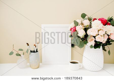Home office desk with photo frame mock up beautiful roses and eucalyptus bouquet in front of pale pastel beige background. Blog website or social media concept .