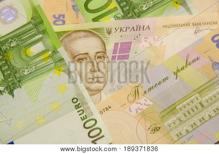 Denominations, face value of five hundred hryvnia, lie together with bills of one hundred euros.