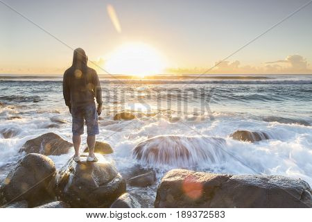 GOLD COAST, AUSTRALIA - MAY 28 2017: Person standing on a rock watching the sunrise over the ocean, with ocean tide cascading over a rock. Burleigh Heads Gold Coast