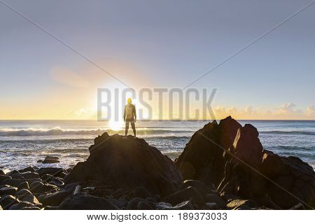 GOLD COAST, AUSTRALIA - MAY 28 2017: Silhouette of person standing in front of sunrise, on a rock at Burleigh Heads Gold Coast.