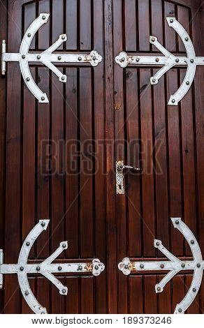 Old brown wooden door with forged hinges. Beautiful background