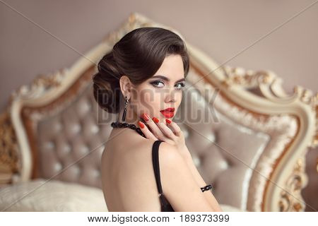 Beautiful brunette, elegant woman portrait. Retro lady with red lips makeup, wavy hairstyle in black sexy dress posing on modern bed in bedroom interior. Luxury life.