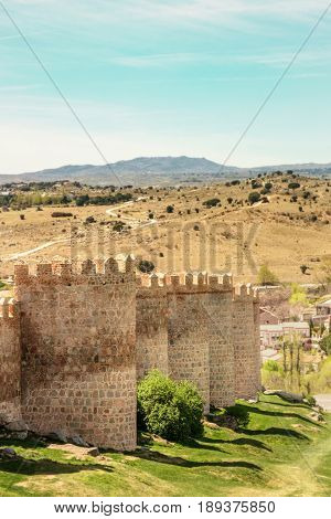 A view over the walls of Avila, an old town in Spain, with mountains in the background