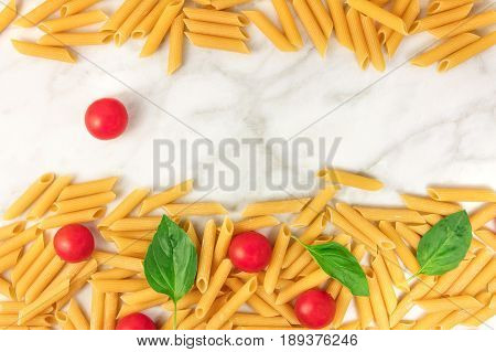 Penne rigate, shot from above on a white marble table with a place for text. An overhead photo of a texture of pasta, basil leaves, and cherry tomatoes forming a frame
