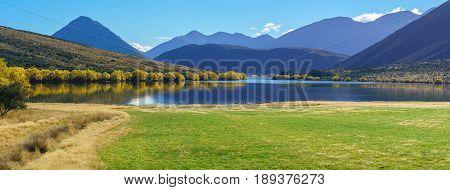 Panoramic image of beautiful scenery of Lake Pearson (Moana Rua) in Autumn Arthur's pass National Park South Island of New Zealand