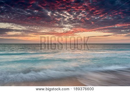 Dramatic Sunset on Sanibel Island showing water motion and teal blue water
