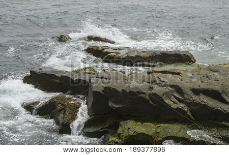 Waves crash over large boulders along the shoreline in Newport Rhode Island