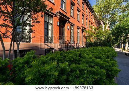 Nineteenth century townhouses with brick facades and wrought iron railings. Summer in Chelsea. Manhattan New York City