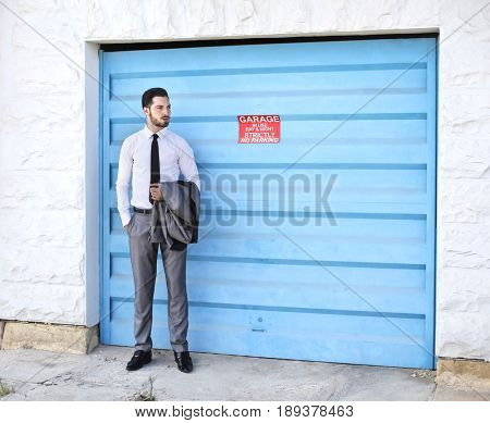 Elegantly dressed young businessman standing and waiting