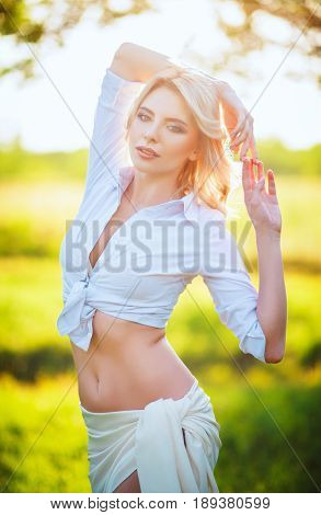Beautiful young woman standing among the meadow