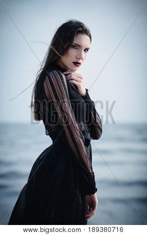 Beautiful sad goth girl in black dress standing on the sea beach
