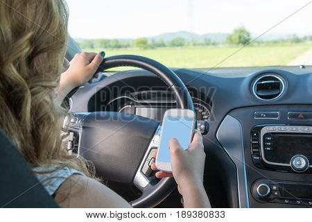 Young driver woman is using a smart phone while driving a car. View from behind the seated driver. All potential trademarks are removed.
