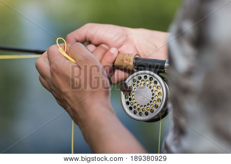 fly fisherman casting his rod on a river, reel closeup