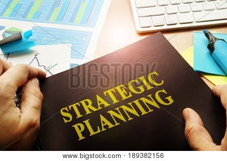 Hands holding documents with title strategic planning.