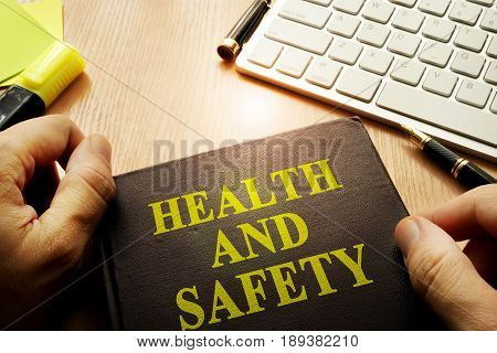Hands holding documents with title health and safety.