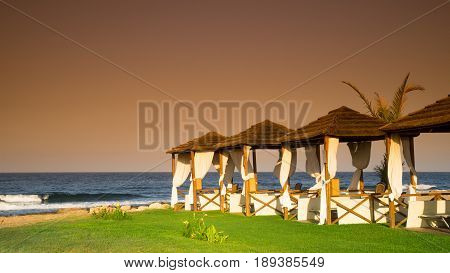 Romantic beach at sunset with pergolas and palm