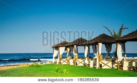 Beautiful romantic beach with empty cabanas and blue sky
