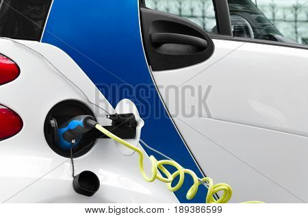 Electric car chargering on the station. Power supply plugged into an electric car being charged. Alternative ecological fuel.
