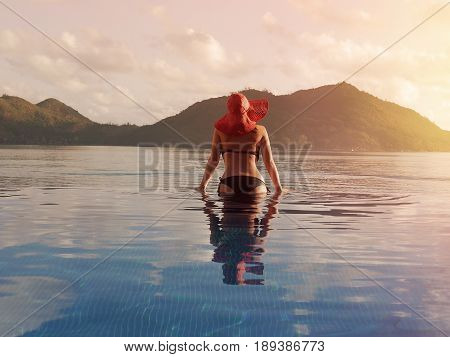 Female  in a red hat in the pool against the backdrop of mountains and ocean.  Tropical Seychelles. Island Praslin