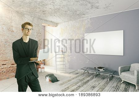 Happy young businessman using laptop in undone room with empty banner on wall and other items. Mock up 3D Rendering
