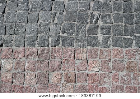 Rubble gray and brown square stones paved road with a horizontal border