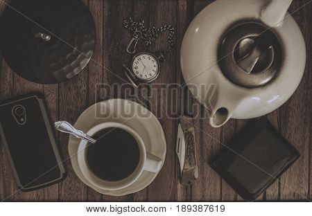 Coffee Tea Pot Cup and saucer pocket knife and watch wallet and cell phone on a wood table.