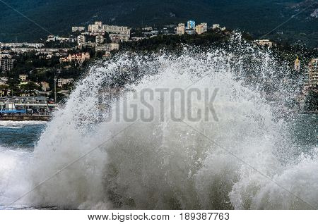 Sea city during a storm on a background of waves