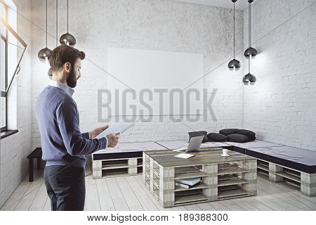 Side view of young businessman holding document in modern white brick interior with furniture and empty canvas on wall. Mock up 3D Rendering