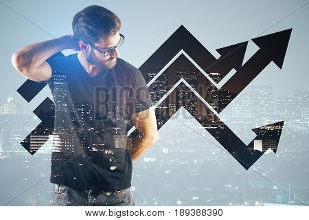Thoughtful young businessman on city background with upward chart arrows. Sales concept. Double exposure