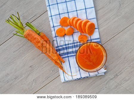 Glasses Of Carrot Juice And Fresh Carrots On Wooden Cutting Board