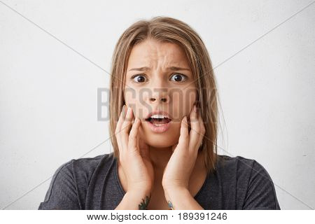 Young Woman Looking With Terror Into Camera Holding Her Hands On Cheeks Isolated Over White Backgrou