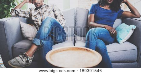 Young displeased black couple.American african men arguing with his stylish girlfriend, who is sitting on sofa on couch next to him with legs crossed.Man looking away offended.Horizontal, cropped