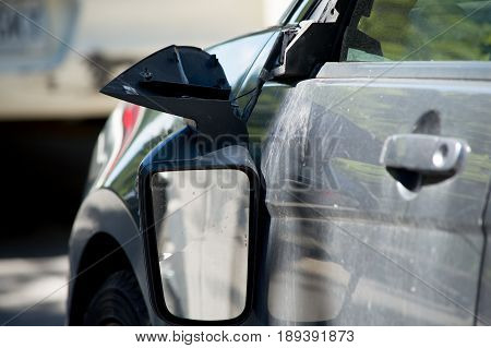 Damaged car after an accident with broken mirror hanging on side of car after collision conceptual insurance claim, mechanic body shop and road safety background photography