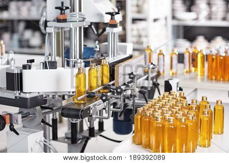 Horizontal Shot Of Cosmetics Or Pharmacy Plant With Automated Equipment. Transparent Plastic Bottles
