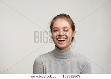 Headshot Of Good-looking Lucky Woman With Tied Hair Pure Skin And Broad Smile Being Happy To Watch A