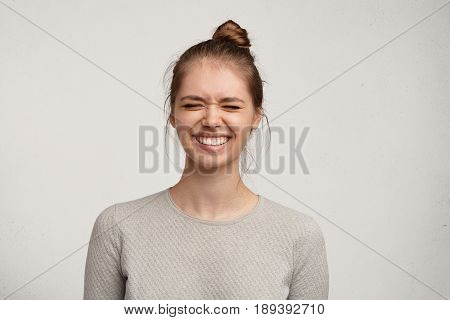 Headshot Of Gorgeous Attractive Young Lady With Hair Gathered In Bun Smiling Broadly And Closing Eye