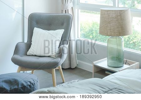 Gray Armchair With Pillow At The Corner Of Bedroom