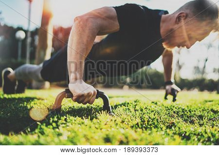 Healthy lifestyle concept.Training outdoors.Handsome sport athlete man doing pushups in the park on the sunny morning. Blurred background