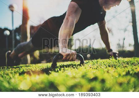 Healthy lifestyle concept.Functional training outdoors.Handsome sport athlete man doing pushups in the park on the sunny morning. Blurred background.Horizontal.Flares, sunlight effect