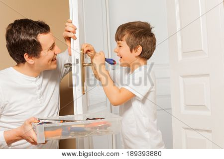 Happy young man holding tool box and helping his kid son to draw up a bolt of door handle at home
