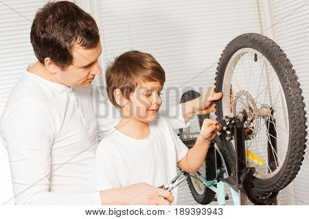 Portrait of young father and his son replacing the brake cable in bicycle brakes using pliers