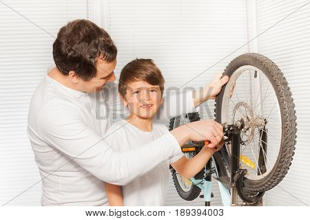 Portrait of happy kid boy helping his father replacing the brake cable in bicycle brakes