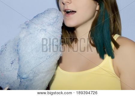 Close Up Of A Girl Eating Cotton Candy On Blue Background.