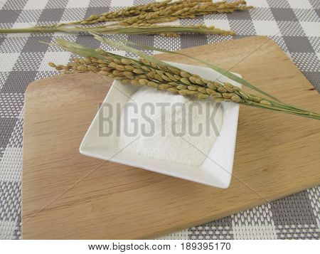 Gluten free rice flour in bowl and rice panicles