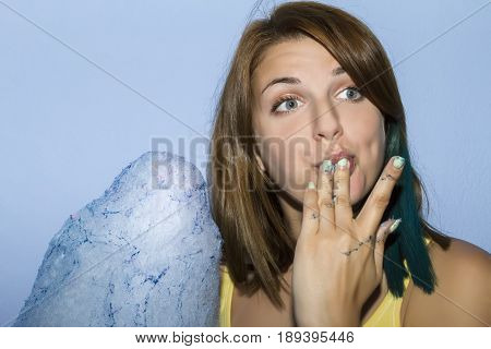 Girl Eating Cotton Candy On Blue Background.