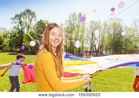 Close-up portrait of pretty blond girl holding the rope of colorful parachute during funny game outdoors at sunny day