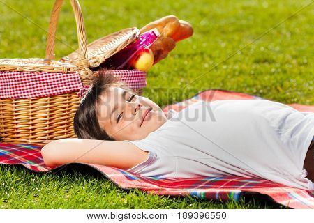 Side view portrait of ten years old boy laying on green grass next to the picnic basket with French baguettes, fruits and beverages