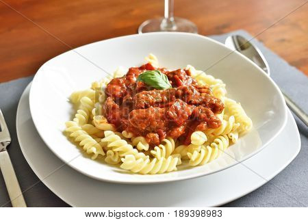 Delicious goulash dish on a white plate with basil leaf. Spiral pasta with tomato sauce.