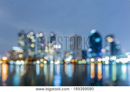 Blurred bokeh city offic building with reflection with twilight sky abstract background