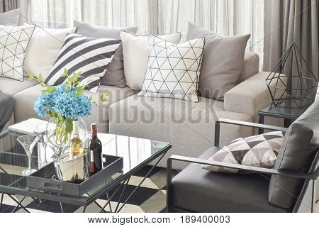 Mix Pattern Pillows In Gray Tone Sofa And Wine Bottles On Center Table In Living Room